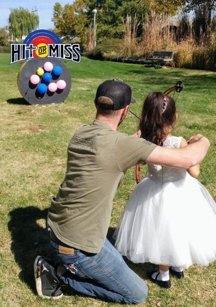 Young girl in a white dress learning to shoot a bow